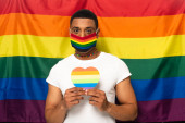 african american man with safety mask and paper heart in rainbow colors on background of lgbt flag