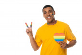 african american man with lgbt flag painted on face, showing peace sign and paper heart in rainbow colors isolated on white