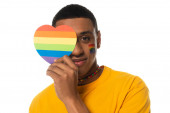 african american man with lgbt flag painted on face, covering eye with rainbow colors paper heart isolated on white