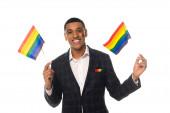afro-amerikai transznemű férfi kezében lgbt zászlók, miközben mosolyog a kamera elszigetelt fehér