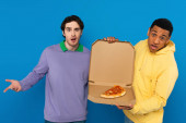 Různé hipsteři držení krabice s pizzu plátek izolovaný na modré