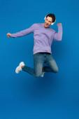 glücklich lächelnder Mann in violettem Sweatshirt genießt Musik und hüpft mit Kopfhörern auf blauem Hintergrund