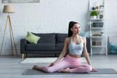 usmívající se žena dívá pryč, zatímco sedí na podložce jógy doma