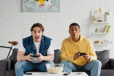 KYIV, UKRAINE - MARCH 22, 2021: excited interracial friends playing video game with joysticks in living room stock vector