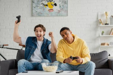 KYIV, UKRAINE - MARCH 22, 2021: young interracial friends playing video game with joysticks in modern living room stock vector