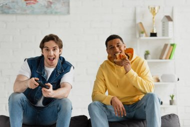KYIV, UKRAINE - MARCH 22, 2021: interracial friends playing video game and enjoying pizza on couch in modern living room stock vector