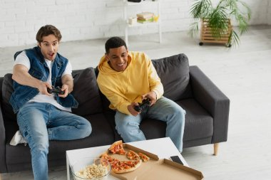 KYIV, UKRAINE - MARCH 22, 2021: high angle view of interracial friends emotionally playing video game with joysticks and enjoying pizza on couch in modern living room stock vector