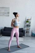 sportovní žena cvičí jógu doma a stojí ve hvězdné póze s rukama za zády