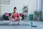 young woman in sportswear training in squatting pose with praying hands