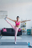 pretty sportswoman looking at camera while exercising in one legged star pose