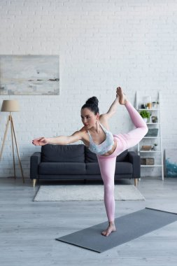 brunette woman standing in lord of dance pose while practicing yoga at home