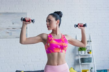 Brunette woman in sports bra looking away while training with dumbbells at home stock vector
