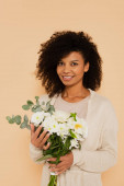 african american woman holding bouquet of daisies and looking at camera isolated on beige