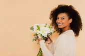 african american woman holding bouquet of daisies and smiling isolated on beige