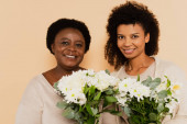 smiling african american adult daughter and middle aged mother with bouquets of daisies looking at camera isolated on beige