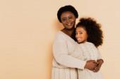 lächelnd afrikanisch-amerikanische Großmutter umarmt Enkelin auf beigem Hintergrund
