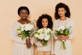 šťastná rodina africké americké babičky, dcery a vnučky s kyticemi květin izolovaných na béžové