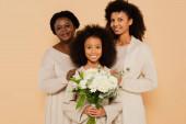 glückliche Familie afrikanisch-amerikanischer Großmutter, Tochter und Enkelin mit Blumenstrauß isoliert auf beige