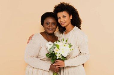 Afrikalı Amerikalı yetişkin kız ve orta yaşlı anne bej rengi bir buket çiçekle dikiliyorlar.