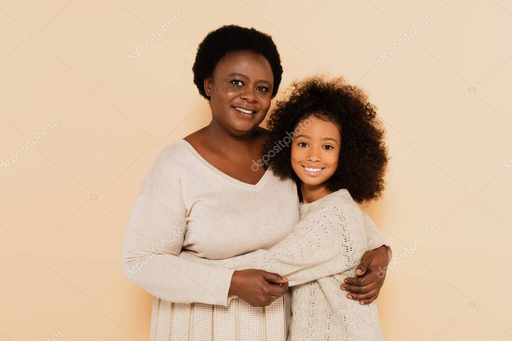 African american grandmother and granddaughter hugging on beige background stock vector