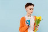 fiatal tetovált nő narancssárga kardigán gazdaság csésze kávé és sárga tulipán elszigetelt kék