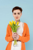 fiatal tetovált nő narancs kardigán gazdaság sárga tulipán elszigetelt kék