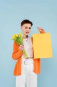 boldog nő tetovált narancs kardigán gazdaság sárga tulipán és bevásárló táska elszigetelt kék