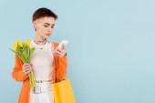 nő tetoválás gazdaság sárga tulipán és bevásárló táska, miközben csevegés okostelefon elszigetelt kék