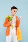 fiatal nő tetoválás gazdaság sárga tulipán és bevásárló táska, miközben csevegés mobiltelefon elszigetelt kék