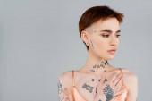 fiatal tetovált nő néz félre elszigetelt szürke