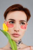 fiatal és tetovált nő rózsaszín szem foltok gazdaság sárga tulipán elszigetelt szürke