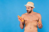 Astonished man in sun hat holding sunscreen isolated on blue