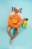 High angle view of happy man holding inflatable ring near suitcase and passports on blue background