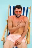 Izgalmas férfi napszemüvegben megérinti a napégést a napozószéken, elszigetelve a kéktől.