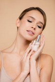 sensual woman with natural makeup and perfect skin posing with perfume isolated on beige