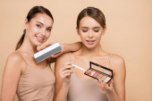 pretty women holding highlighter and eye shadows palettes while posing isolated on beige