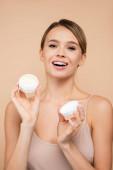 boldog nő kozmetikai krém mosolygó kamera elszigetelt bézs
