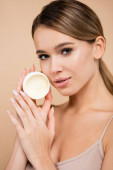 érzéki nő kezében kozmetikai krém, miközben néz kamera izolált bézs