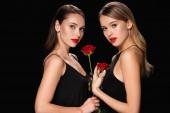 junge Frauen mit leuchtend roten Lippen posieren mit Rosen isoliert auf schwarz