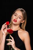 érzéki nő pózol vörös rózsa és szirom elszigetelt fekete