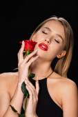 sensual woman with closed eyes posing with red rose isolated on black