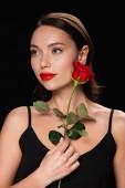 csinos nő piros rózsa néz el elszigetelt fekete