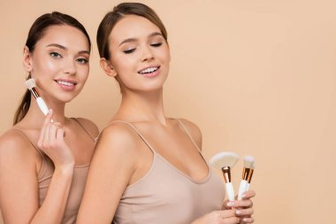 Smiling women with natural makeup posing with cosmetic brushes isolated on beige stock vector