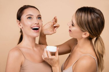 Pretty woman applying face cream on excited friend isolated on beige stock vector