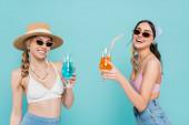 Positive Frauen in Tops und Sonnenbrille mit Cocktails auf blauem Grund
