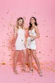 Pretty women holding champagne under golden confetti on pink background