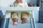 oříznutý pohled na bosé africké americké dítě sedící v kojeneckém křesle, rozmazané pozadí