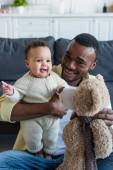 boldog afro-amerikai férfi kezében teddy maci közel vidám baba