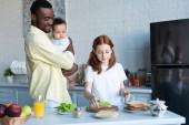 kiskorú gyerek készít szendvicsek közelében afro-amerikai apa és a csecsemő húga