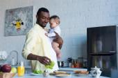 boldog afro-amerikai férfi kezében baba lány, miközben elkészíti szendvicsek reggelire